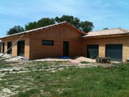 Photo d'une maison en bois réalisée par Cogebois avec son garage double portes, toit en tuile